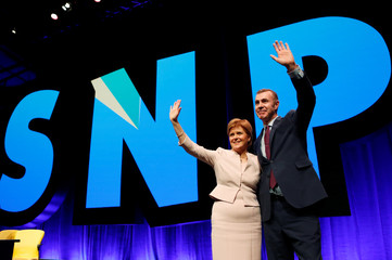 Scotland's First Minister Nicola Sturgeon waves with Plaid Cymru's leader Adam Price at the Scottish National Party's party's conference in Glasgow, Scotland