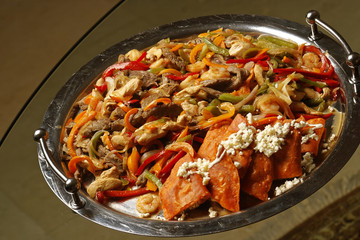 Grilled beef and chicken with peppers, onions and cheese.