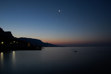 Black sea sunrise with the Moon and morning star