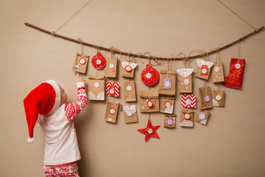 child looks at the advent calendar. Baby girl in a Christmas hat and pajamas shows on first gift