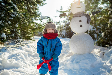 Little boy plays in snow and makes snowballs near large snowman