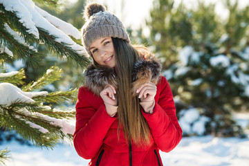 Attractive young woman in hat and sporty red coat smiles on winter snowy landscape