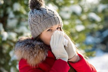 Young woman sneezes in paper handkerchief in winter outdoor