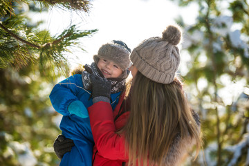 Attractive young mother hugs her son  in winter forest
