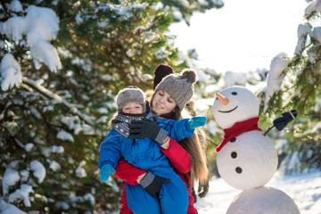 Happy young mother and her son have fun in winter. Play in snow and make snowman