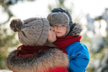 Mother kissing son in winter