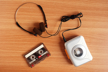 Old portable cassette tape player and headphones on wooden floor