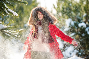 Attractive young woman in hat and sporty red coat smiles plays with snow in the forest