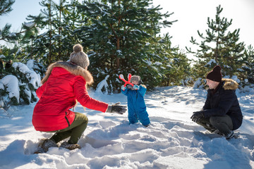 Father, mother and son play in snow in winter park. Happy winter holiday