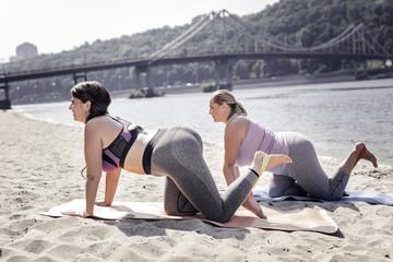 Great mood. Joyful cheerful women lying on yoga mats while exercising together on the beach