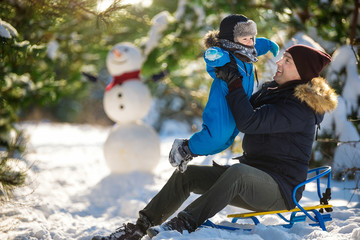Father sits on sledges and holds little son in snow winter wood