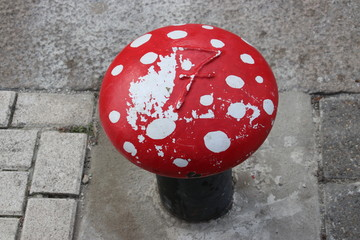 Bollard in the Wijnhaven harbor in Rotterdam painted as fly agaric mushroom .