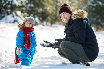 Father and little son play in snow winter wood