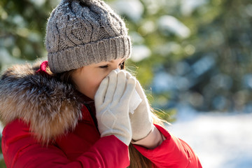 Young woman is sick in winter and sneeze