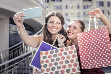 Successful shopping. Happy delighted women showing their bags while taking photos together