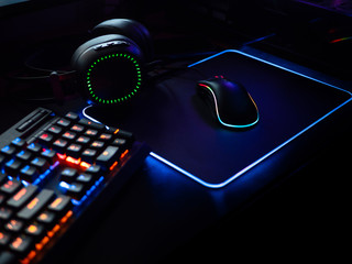 gamer workspace concept, top view a gaming gear, mouse, keyboard, joystick, headset, mobile joystick, in ear headphone and mouse pad on black table background.
