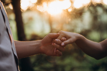 Sun shines over man and woman holding each other hands tender