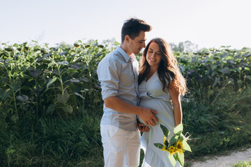 Happy man holds his arm on pregnant woman's belly standing on the path across the field of sunflowers