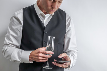 Well dressed man in white shirt and black suit vest holding a glass of champagne and texting with smart phone. Concept for being bored at a party. White background with copy space for text.
