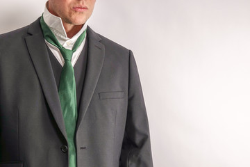 Well dressed man in white shirt and black suit get dressed / undressed. Shirt collar unfold. White background with copy space for text.