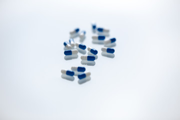 Closeup of a bunch of blue and white medication pills on a white background
