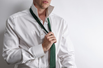 Well dressed man in white shirt get dressed / undressed. Shirt collar unfold and corrects his tie. White background with copy space for text.