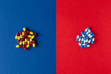 Contrast of colourful medication pills on blue and red colour background