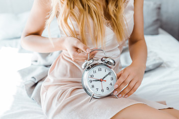 cropped shot of young blonde woman sitting on bed and holding alarm clock