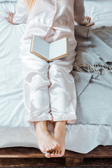 cropped shot of young woman in pajamas sitting on bed with book