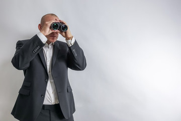 Businessman in white shirt and black suit scouts in binoculars. Concept for job search and long term unemployment, LTU. White background with copy space for text.
