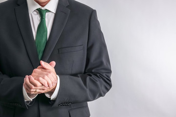 Well dressed businessman in white shirt and black suit. Put his hands together in a soothing, calming and clear body language. White background with copy space for text.