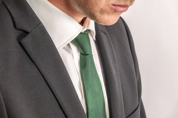 Close up of well dressed businessman in white shirt, green tie and black suit.