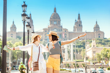 Two young happy women tourists friends hugging against the background of the National Museum of Art near the Plaza of Spain and the Montjuic Fountain in Barcelona