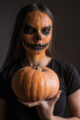 Portrait of a girl in a terrible make-up in honor of Halloween on a black background with a pumpkin