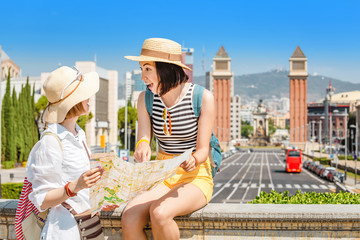 Two happy tourists looking at the map while traveling in Barcelona, near Venetian Towers and Spain Square