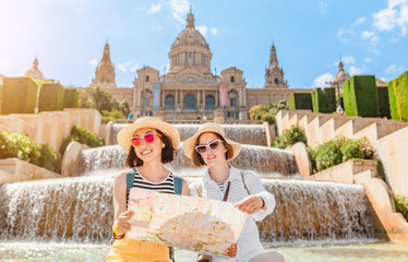 Self adhesive Wall Murals Barcelona Two young happy women tourists friends hugging against the background of the National Museum of Art near the Plaza of Spain and the Montjuic Fountain in Barcelona