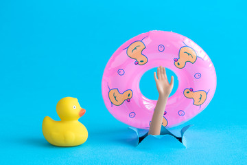 Small rubber duck and doll hand from the water with inflatable pool float minimalistic abstract.