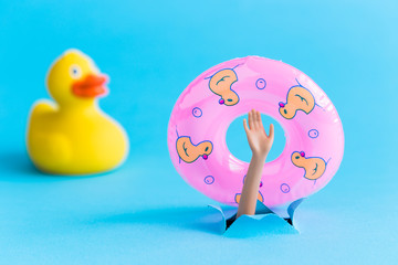 Rubber duck next to doll arm holding inflatable pool float and emerging from blue paper background. Drowning minimal creative abstract concept.