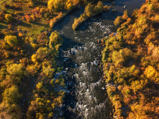 Aerial view of the river and color trees, sunny autumn landscape, drone shot. National park Bugski Guard with picturesque valley and Southern Bug river, Mykolaiv region, Ukraine