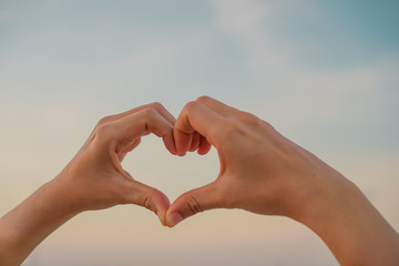 Woman hand do heart shape on nature blue sky background.