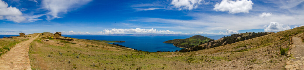 Panoramic on Isla del Sol with a road made of stones, the Titikaka Lake and small constructions on a sunny day