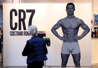 A woman stands in front of Juventus soccer player Cristiano Ronaldo underwear advertising panel in downtown Milan