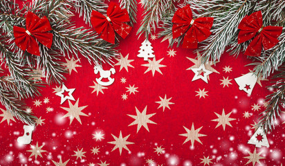 Red Xmas background with stars. Fir branches with red bowls. Top view. Snow effect
