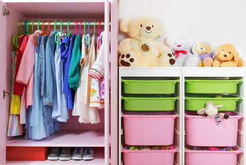 Wardrobe in the children's room. Storage system and storage for the concept of children's things and toys.