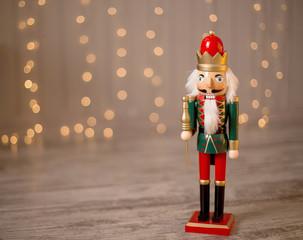 Toy nutcracker on a festive background