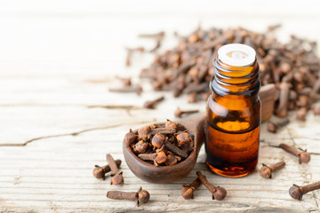 clove essential oil in the glass bottle, on the wooden board