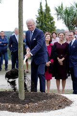 Sweden's King Carl XVI Gustaf plants a tree as Sweden's Crown Princess Victoria, Prince Daniel, and Queen Silvia look on during a ceremony at the Parc Beaumont in Pau