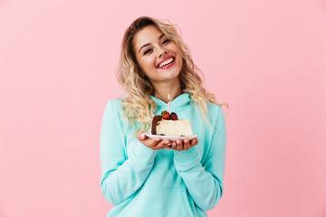 Photo of happy woman in basic clothing holding piece of birthday cake with candle, isolated over pink background