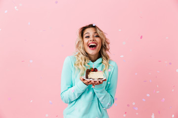 Photo of pretty woman in basic clothing holding piece of birthday cake with candle, isolated over pink background