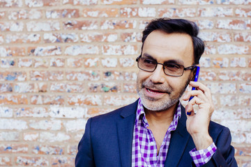Portrait of an entrepreneur on the phone in front of a brick building
